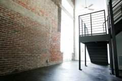 Second floor metal staircase leading to loft bedroom area at The Lofts San Marco